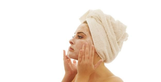 woman applying face cream after shower