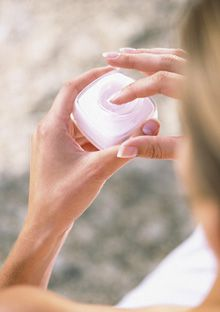 woman dipping her hand in cream jar